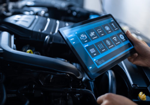 Car Service Manager or Mechanic Uses a Tablet Computer with a Futuristic Interactive Diagnostics Software. Specialist Inspecting the Vehicle in Order to Find Broken Components In the Engine Bay.